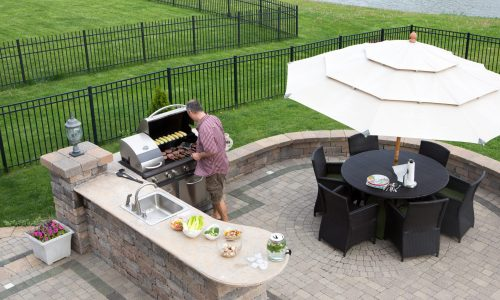 High angle view of a man cooking meat on a gas BBQ standing in the sunshine on a paved outdoor patio at the summer kitchen preparing for guests with a table and chairs with a garden umbrella alongside