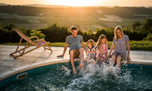 Young happy family having fun while splashing water with their legs in the pool.